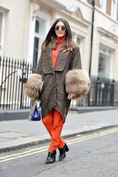 Anisa Sojka styles vintage Matthew Williamson orange roll turtleneck trouser suit | Brown tweed oversized coat with fluffy fur sleeve cuffs | Red, blue and green Dolce and Gabbana patchwork mini sicily handbag | Black round Rayban classic sunglasses | Paper Doll ankle boots | Blogger street style shot during London Fashion Week by David Nyanzi