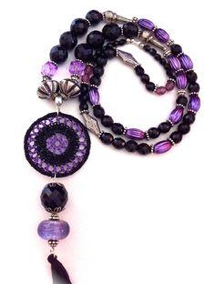 Collar XLL con 1 rosetón en croxet, en violeta y negro, rematado con bola de cristal facetado negro, bola de cristal de murano violeta y pompón negro. Tira compuesta de piezas de resinas violetas, cristales facetados negros de diferentes medidas. Intercalados con piezas y anillas metálicas. 25€