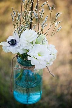 """Hanging mason jars filled with a mix of """"wild"""" flowers lined the asile..."""