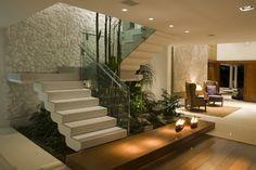 Sala com jardim de inverno e escada com guarda-corpo em vidro.