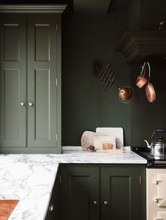Hunter green cabinets, soft white marble and copper pots give this kitchen its quintessential English charm. | Designer: Plain English