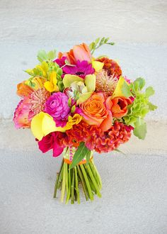 BLOSSOM SWEET : flowers used in bouquet: callas, cymbidium orchids, roses (two varieties), freesia, celosia, tulips, bells of ireland, pincushion protea, gerbera daisies, ranunculus