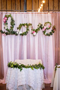 Behind our sweetheart table was draped fabric, and a six foot Love sign, which I along with a family friend made. It was wire bent to spell the word LOVE.  We wrapped lights around it and put all these silk flowers and leaves. It was beautiful, and I had never seen something like it before. Spring Barn Wedding - Bethaney Photography. Click http://www.confettidaydreams.com/romantic-spring-barn-wedding/