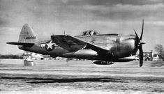 A USAAF P-47 Thunderbolt at extreme low level. Note that the sweep of the camera's pan has bent the buildings in the background.