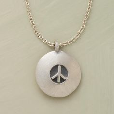 "CHARMS FOR PEACE NECKLACE -- A delicate emblem of a most weighty sentiment make gifts of great impact. Brushed sterling silver pendant is suspended from a polished sterling chain. Handcrafted. Exclusive. 20""L."