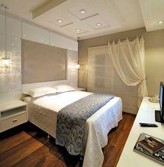 O casal queria um quarto confortável, prático e sofisticado, que combinou madeira e branco no ambiente. O painel atrás da cama foi feito com módulos em laca fixados na parede.