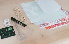 Material - DIY: Windrad als Tischkarte - - einige Bögen buntes Papier (zum Beispiel gemustertes Scrapboking Papier) - weißes Papier - Schaschlikspieße - Verschlussklammern - Nadel - Schere - Geodreieck - Bleistift Bild: © Fräulein K...