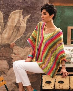 Lacy bands in dazzling yellow, lime and fuchsia make the essential blanket poncho ready for warmer climes. The front and back are knit side to side in Taiyo colorway alternating panels of eyelet mesh, stockinette and zig zag lace that are divided by p Crochet Poncho Patterns, Knitted Poncho, Crochet Scarves, Crochet Shawl, Crochet Clothes, Crochet Stitches, Knit Crochet, Knitting Patterns, Crochet Vests