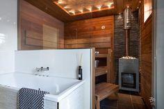 Kylpyhuoneen ja saunan välinen lasiseinä avartaa tilan