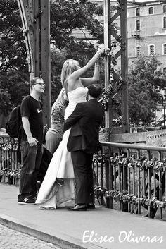 Amor sellado con un candado joven y hermosa novia polaca, sostenida en el aire por el novio, mientras coloca un candado en los hierros del puente que conduce a la catedral de Wroclaw (Polonia) tras la ceremonia núpcial como símbolo de su inquebrantable amor. La barandilla metálica del puente está repleta con cientos y cientos de candados de otras parejas