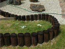 Nízká zvlněná ohrádka z dřevěných kuláčů, vlastně palisáda navazující na oplocení vzadu. V tomto případě plní funkci letního výběhu pro dvě želvy, kterým se v tomto teplém koutě zahrady neuvěřitelně daří.