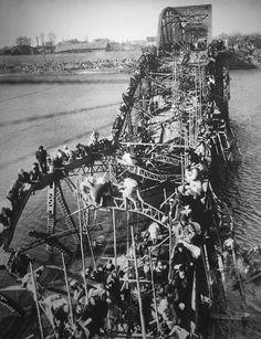 Refugees cross a destroyed bridge during the Korean War, October 1950.