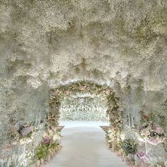 A tunnel coated in baby's breath and subtle pops of pastel #blooms creates a cloud-like environment for the dreamiest of #wedding entrances. Repost: @joerainforest