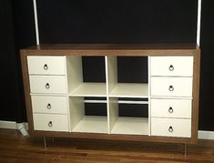 Materials: 1 Expedit 2x4 (white), 4 Sets of Expedit 2 Drawer Inserts (white), Capita Legs, Faux Wood Grain Contact Paper, 8 Ring Pulls (brass)Description: Thi