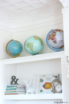 I love the pops of color from these globes against the white walls. Lots of amazing ideas for decorating with globes.