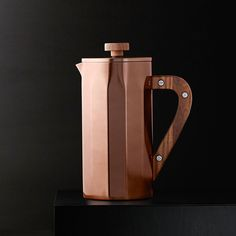 A double-walled stainless steel coffee press with walnut accents and included timer and scoop.