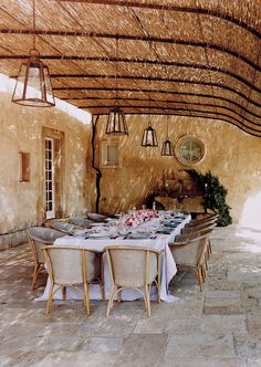 A vine-shaded terrace at the home of Janet de Botton in the South of France, highlighted with a linen tablecloth found at Léron. Photographed by François Halard, Vogue, September 2004.