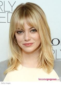 Emma Stone wears her shoulder-length medium hair with lots of face-framing layers and whispy bangs.