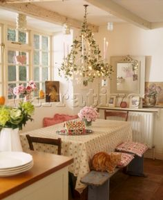 A country kitchen with dining area  decorated for Christmas  table  bench seat  candle chandelier  t