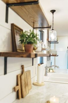 Open shelving in Kitchen with shiplap walls and marble countertops