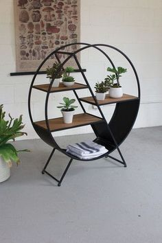 Kalalou Metal And Wood Round Shelf - Staggered shelves within a round frame set the stage for creative displaying. The black iron nicely contrasts with the rich natural wood finish. For those of you with a green thumb, find a nice sunny spot for this open backed sphere.