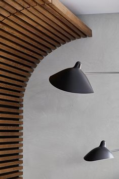 A close-up look at the wood slat wall where it curves towards the ceiling and meets the wall.