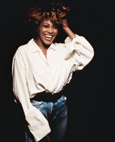 One of our favorite shots of the queen of rock 'n' roll—Tina Turner captured mid-laugh in an oversize shirt tucked into high-waisted jeans. Such beautiful ease!