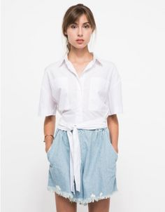 From Stelen, a lightweight minimalist cropped top with waist tie in white. Features collar, button up panel, hidden buttons, exposed top button, double chest pockets, functional waist tie, high-low hem, finished edges with loose fit throughout.  • Light