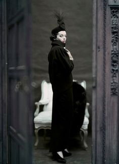 Clad in an outfit by Adele Simpson, a model regards the camera through an opened door. Her high-collared dinner jacket slants into her hips, while the narrow skirt has small slits. The muted color scheme and slightly murky look of the image makes it similar to a painting. John Rawlings's photograph appeared in the November 2, 1951, Vogue.