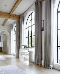 Chestnut Hill Home Floor to ceiling drapes around these arched black window frames. Arched Window Coverings, Curtains For Arched Windows, Modern Window Treatments, Window Treatments Living Room, Living Room Windows, Floor To Ceiling Windows, House Windows, Arch Windows, Wall Drapes