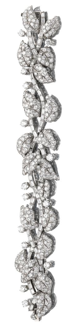 DIAMOND BRACELET, CIRCA 1960.  The articulated band of foliate design set with brilliant-, single-cut  and baguette diamonds, further highlighted with brilliant-cut diamonds, mounted in platinum, length approximately 190mm.
