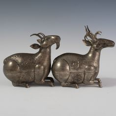 "Lot #214: Pair of Cambodian Silver Animal Boxes  DESCRIPTION:Pair of Cambodian 90% silver animal boxes. Features a goat and an elk figurines whose bodies open to reveal interior. Engraved with inricate floral and paisley designs. Marked: ""90%""  CIRCA:19th-20th Ct. ORIGIN:Cambodia DIMENSIONS:Elk: H:6″ L:6″ W:3″ Total Weight: 235 grams Goat:H:5.5″ L:5.5″ W:2.75″ Total Weight: 200 grams"