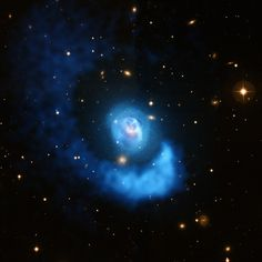 Abell 2052: A Galaxy Cluster Gets Sloshed The hot gas in the galaxy cluster Abell 2052 is being sloshed back and forth like wine in a glass. The sloshing was set in motion when a small cluster smashed into the larger central one.  The large spiral structure on the outside of the image was also caused by that off center collision. Sloshing of hot gas like this can affect how the giant elliptical galaxy and its supermassive black hole at the center grow.