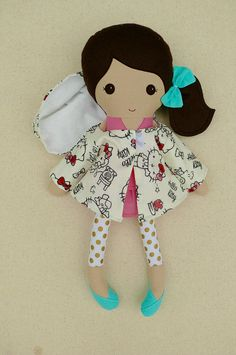 Custom listing for Anna:  This is a handmade cloth doll measuring 20 inches. She is wearing a sweet, pink, ruffled dress with gold polka dotted leggings, and turquoise shoes. In addition, she has a removable, hooded jacket with a velcro closure. Her dark brown hair is worn in a low, side ponytail and accented with a matching, aqua, fabric bow. She is made from 100% cotton fabrics, wool blend felt, and polyester fiberfill. Her seams are triple stitched and she is firmly stuffed with Polyfil…