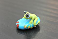 Finn the Green Frog on a Flattened Blue Bead Artisan Handmade Glass Frog Bead by blancheandguy on Etsy