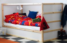 KURA reversible bed shown as a low bed with colorful bedlinen