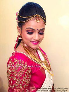 Traditional Southern Indian bride, Kruthika wears bridal silk saree and jewellery for her Muhuratam. Makeup and hairstyle by Swank Studio. Maang tikka. Pink lips. Jhumkis. Eye makeup. Silk sari. Tamil bride. Telugu bride. Kannada bride. Hindu bride. Malayalee bride. Bridal Saree Blouse Design. Indian Bridal Makeup. Indian Bride. Gold Jewellery. Statement Blouse.  Find us at https://www.facebook.com/SwankStudioBangalore