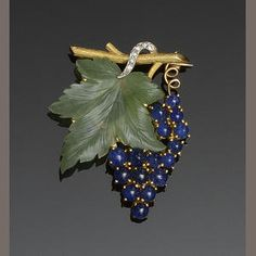 A green-hardstone, diamond, sapphire and gold brooch in the form of a fruiting vine, a symbol of hospitality and well-being. (Bonhams)