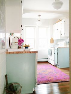 Pink Persian rug and light blue cabinets in kitchen