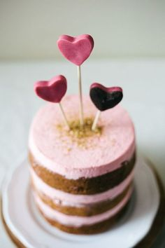 Image #1:  Lanie's naked cake idea.  We'd like white frosting to replace the pink.  Large enough to hold five lit sparklers.  Would love to see the disco style glitter here as well.  If there is a way to do these same hearts  mixed in with the sparkers at different heights that would be awesome!  Would like the hearts to be a bright peachy coral color.