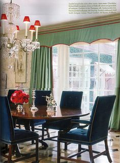 I love the colors in this space.  I've seen so many turquoise/sea foam green and red rooms lately.  The navy blue chairs are a nice change.