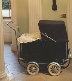 Le Nouveau Ne gave each doll a pram and cot.  Both prams were dark blue, with white satin-bound fur covers.