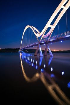 Cross the Infinity Bridge at night. Located in Stockton-on-Tees, England  -- The pedestrian and cycling bridge has light sensors on it, so as you walk across they light up and then slowly fade leaving a light trail behind you. #travel #bucketlist