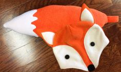 Fox hat and tail - made from fleece :)  Don't need much to make it, either -- 3/4 yard of orange fleece, FQ white fleece, 1″ x 1″ of black fleece (for nose), 2 black buttons (for eyes), stuffing :D