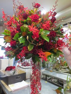 Tall arrangement in vivid reds creating with Roses and Orchids.