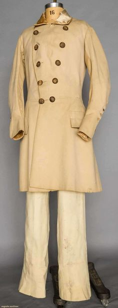 """MAN'S SUPER-FINE WOOL COAT/SURTOUT, AMERICAN, 1820s .  Beige wool broadcloth, fitted through chest, tan velvet collar & turn back cuffs, diagonal double row of brown thread buttons, side & F waist seam, double pleats to wide back skirt, CH 40"""", L 39"""",  Note the location of the pocket flaps, the velvet lining to the cuffs, the fishes inset into the sleeves."""