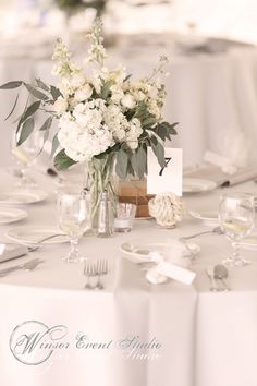 Centerpieces of hydrangea, seeded eucalyptus, spray roses, and creamy stock in vases paired with stacks of vintage books
