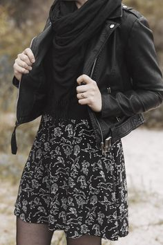 black astrology print dress with a sweater layered over and a biker jacket