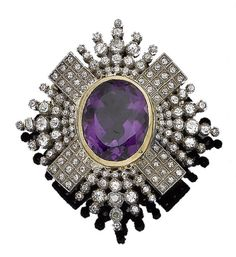 An amethyst and diamond brooch, by Carlo and Arthur Giuliano Designed as a starburst, collet-set to the centre with an oval mixed-cut amethyst, within a radiating surround of cushion-shaped and old brilliant-cut diamonds, diamonds approx. 1.95cts total, maker's mark C&AG.