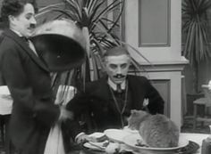 Charlie Chaplin serves a customer in a restaurant, not realizing there is a cat under the cloche, in the classic comedy short The Rink (1916).